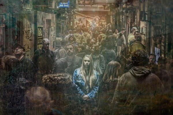 Mujer en la calle entre mucha gente. Está triste, deprimida