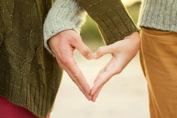 Pareja que une sus manos formando un corazón. Imagen romántica, pareja que se quiere