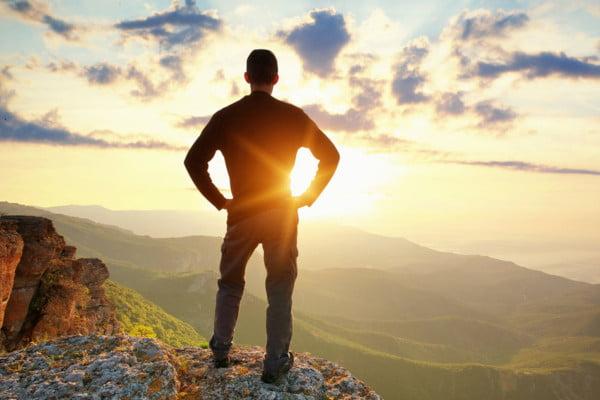 Adulto en la naturaleja, de espaldas mirando una puesta de sol. Da sensación de calma, la que buscan las personas que acuden al psicologo para adultos