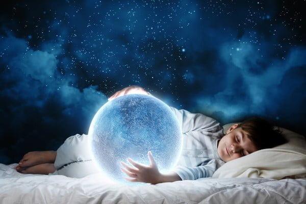 Insomnio vs sueño satisfactorio. El niño duerme en su cama abrazando la luna llena