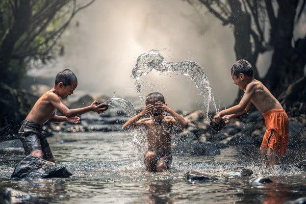 Relaciones sociales y familiares, niños jugando en un río