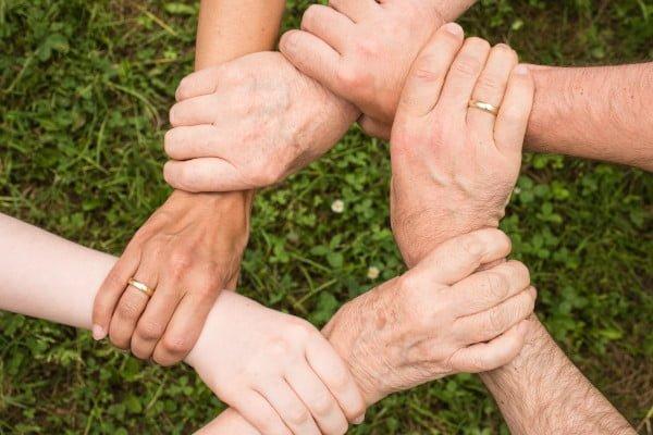 La familia funcionando como un equipo, se sujetan las manos entre sí formando un círculo