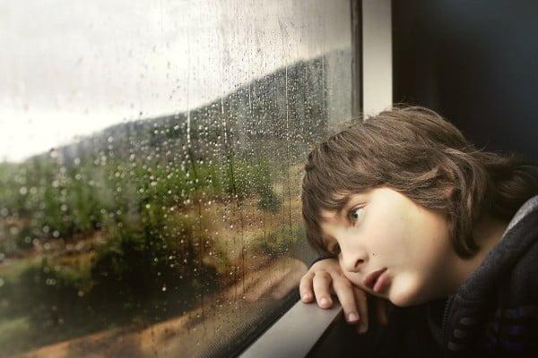 Traumas, duelos y adaptación al cambio, niño triste mirando por la ventana